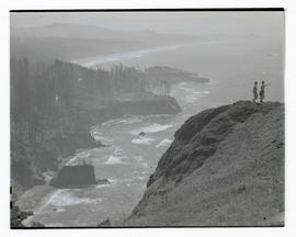 Two women on headland with view of ocean coastline