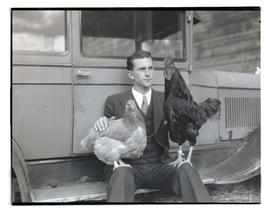 Man with hen and rooster