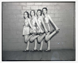 Four tap dancers posing in a line