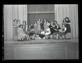 Marylhurst College students on stage, posing with books, 1944?