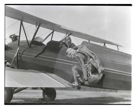 Dorothy Hester on wing of biplane, wearing parachute