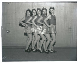 Five tap dancers posing in a line