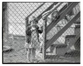 Two unidentified young girls looking through fence