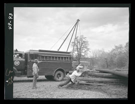 Men pushing wooden utility pole