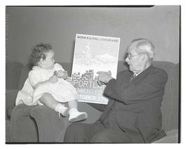 Man showing Portland Community Chest poster to baby