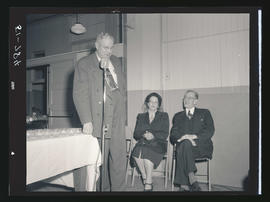 Man speaking at microphone with two other seated individuals