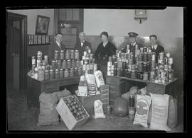 Five unidentified people posing with food in Pullman Company office, Union Station, Portland