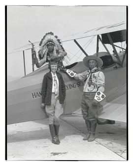 Kiutus Tecumseh and his father posing with unidentified woman and plane