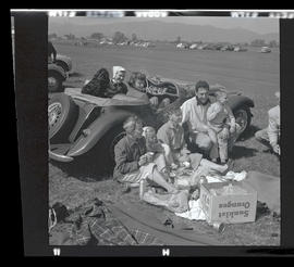 Adults and children picnicking next to car at auto races in Tillamook, June 1955