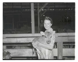 Unidentified girl holding calf, probably at Pacific International Livestock Exposition