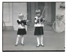 Two young girls holding violins