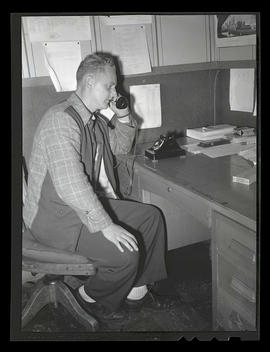Worker using telephone during swing shift, Albina Engine & Machine Works, Portland