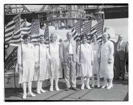 Man and group of women posing with flags during event aboard ship?