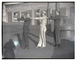 Three girls in usher costumes, posing on rooftop