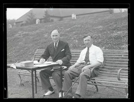 Two unidentified golfers? seated on bench