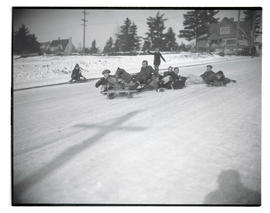 Children sledding on street