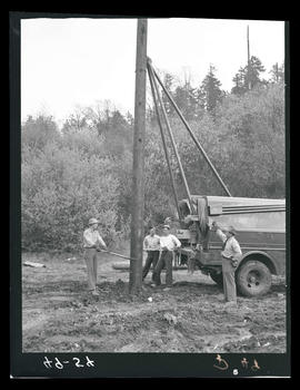 Men with wooden utility pole