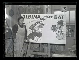 Worker posing next to sign with caricatures of Tōjō, Hitler, and Mussolini at Albina Engine &...