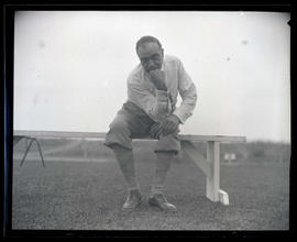 George L. Baker seated on bench at golf course