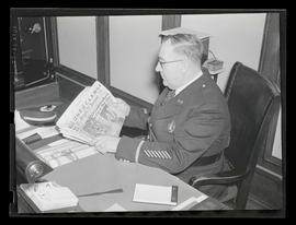 Portland police captain reading Oregon Journal
