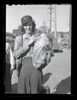 Tess Wilson holding sack of corn during market at Albina Engine & Machine Works, Portland