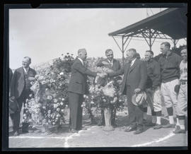 Men shake hands during ceremony on baseball field