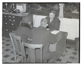 Charles F. Walker? seated at desk with two unidentified people