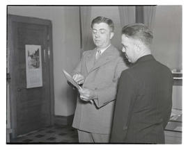 Charles F. Walker? showing document to unidentified man