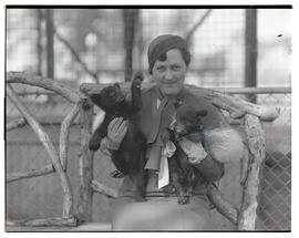 Unidentified woman holding two bear cubs