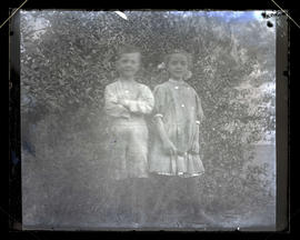Two children in front of bush, full-length portrait