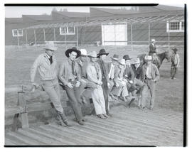 Men leaning on fence, possibly at livestock show