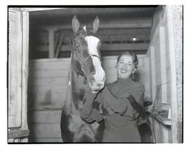 Woman and horse in stall