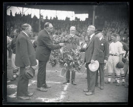 George Baker and unidentified man hold flower arrangement at home plate ceremony