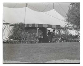 Two unidentified women outside large tent, possibly at plant show