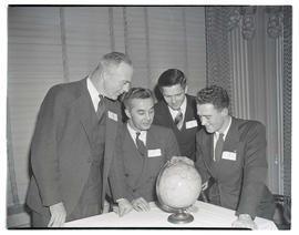 Four unidentified men looking at globe