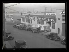 Men and trucks outside Ballif Distributing Company, Southeast 2nd Avenue, Portland