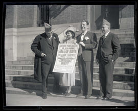 George L. Baker and Joseph K. Carson with two unidentified people holding sign for earthquake ben...