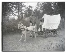 Children with goat harnessed to small covered wagon