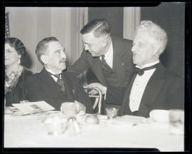 Unidentified man, Joseph K. Carson, and B. F. Irvine at meal