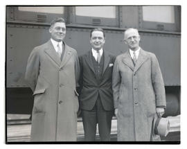 Three men next to train car, possibly at livestock show