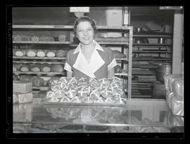 Bakery employee with tray of hot cross buns
