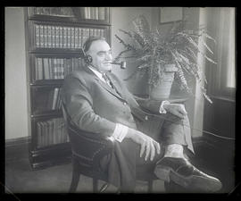 George L. Baker, sitting in chair and wearing headphones
