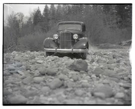 Car driving on rocks, possibly near river