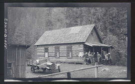 Oak Grove project, group of people standing in front of a wooden cabin