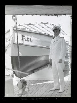 Unidentified U.S. Navy officer posing with boat, the Rel