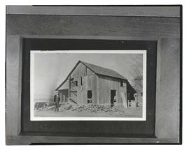 Photograph of two unidentified people with damaged wooden building