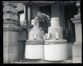 Joseph K. Carson and unidentified man with bricks and concrete cylinders on steps at city hall