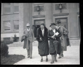 Dr. and Mrs. Howard with two unidentified people, walking away from building