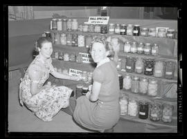 Two young women in front of canned food display