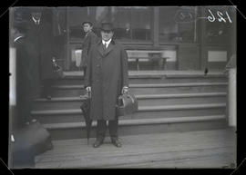 Unidentified man holding valise and umbrella